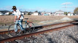 a bicyclist makes his way down the railroad tracks