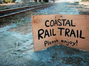 the hand-painted wooden sign was broken and left beside the wooden post where it welcomed bicyclists to the Santa Cruz Coastal Rail Trail