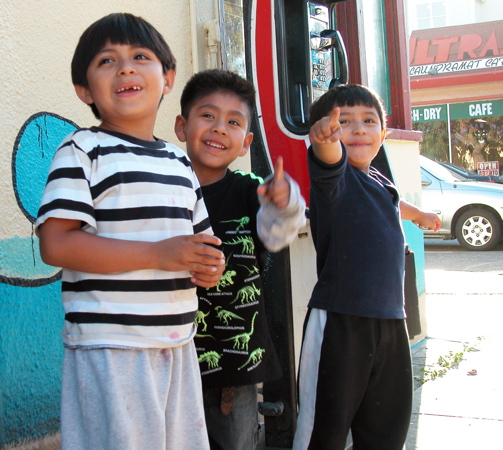 young boys watch the demonstration go by and point in excitment