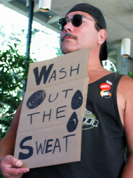 """a worker holds up a sign that reads, """"Wash Out the Sweat"""""""