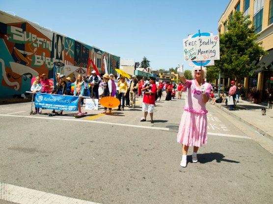 """Santa Cruz peace activist Sherry Conable stands on Cathcart at Pacific holding up two fingers for peace and a placard stating """"Free Bradley Manning. Peace Hero""""."""