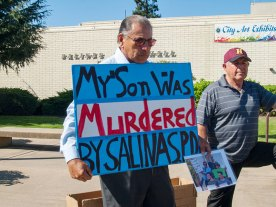 "Frank Alvarado Sr. holds a sign on October 1, 2014 in front of Salinas City Hall reading, ""My Son Was Murdered By Salinas PD."" Frank Alvarado Sr. is also displaying a photo of his son, Frank Alvarado, who is holding a sign on May 14, 2014 stating ""Invest in Protecting and Healing, Not in Caging"" before speaking at a Sin Barras rally at the Santa Cruz Courthouse for building strong communities in California, not more jails!"