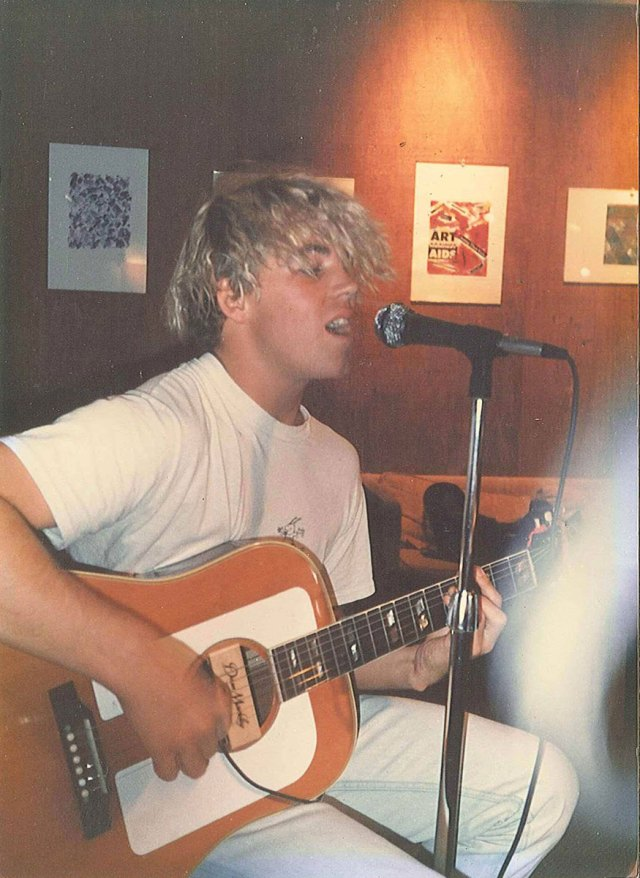 """Photo of Bradley Nowell shared by Reid Clow who writes, """"One of the main reasons I went to UC Santa Cruz was because Bradley Nowell from Sublime attended the school for his freshman and sophomore years of college. Here is a picture of him strumming what was probably an """"X"""" cover at the Stevenson Café in the 88-90 period."""""""