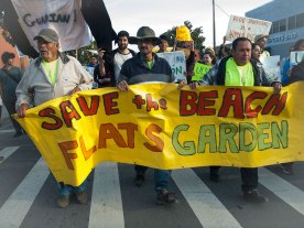 Beach Flats Gardeners, including Don Emilio Martinez Castañeda (left) who has been cultivating in the garden since it began over twenty five years ago, lead the march up Pacific Avenue and they cross Laurel Street in downtown Santa Cruz.