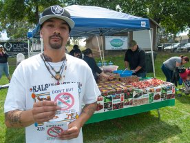 Michael Garcia of the Watsonville Brown Berets holds a boycott Driscoll's flyer in front of the Driscoll's booth at Watsonville Earth Day on April 24, 2016.