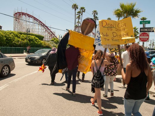 Supporters of the Beach Flats Community Garden march on Beach Street in Santa Cruz in front of the Giant Dipper rollercoaster at the Beach Boardwalk as part of a campaign to save the garden.