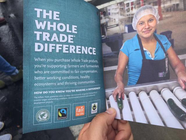 """Photo by Xolotl Edgar Franx. May 28, 2016. A manager at the new Whole Foods Market in Bellingham, WA gave supporters of Families United for Justice and the international Driscoll's Boycott a booklet with information on """"The Whole Trade Difference"""" when they were holding signs and distributing flyers in front of the store. Original photo caption by Xolotl Edgar Franx: More """"fair trade"""" labels, no justice for farm workers."""