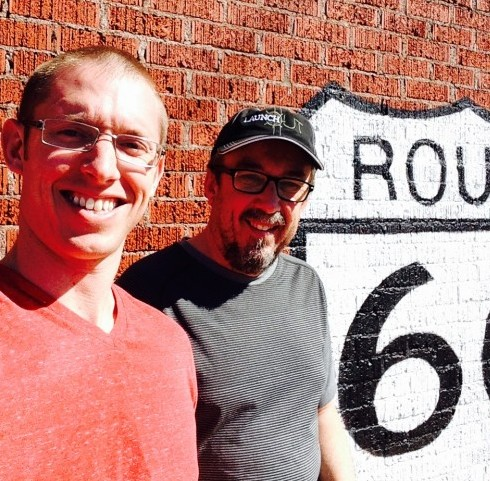 Bradley and Randy smiling for a photo in front of a Route 66 sign.