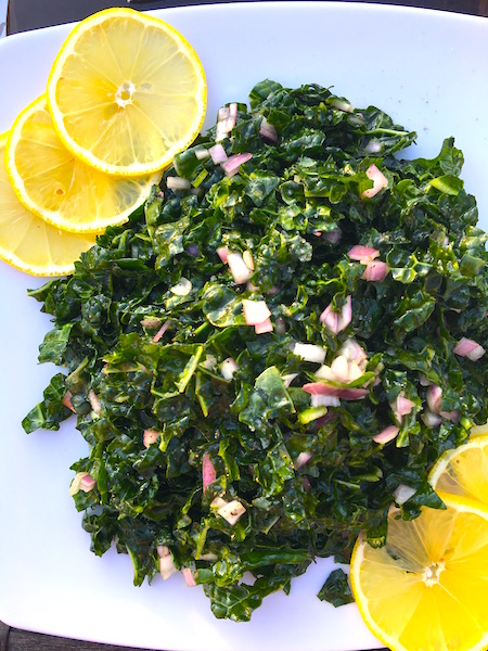 The Best Kale Salad Recipe served on a plate with lemon wedges for garnish.