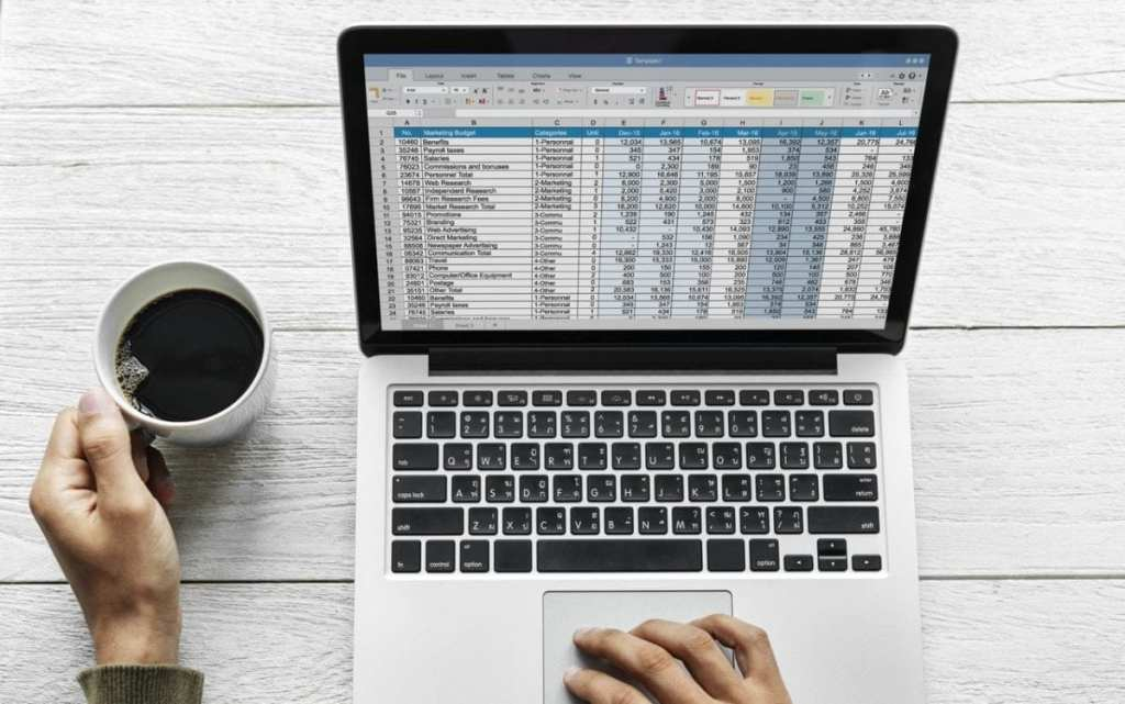 Man drinking coffee and preparing a marketing budget with spreadsheets on laptop