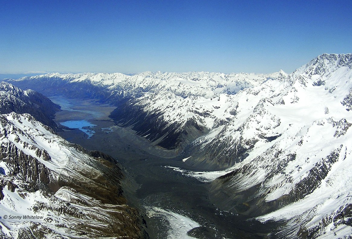 Facing South: Tasman Glacier (foreground – darker areas are moraine gravels  over the ice) on the eastern side of Aoraki Mt Cook (right), and Tasman River (centre back).