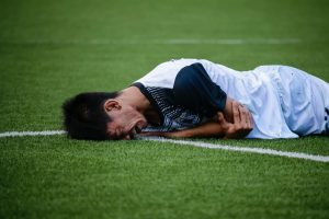 Make soccer player injured laying on the field face down holding his arm crying