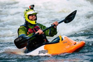 Man in a kayak white water rafting adventure wearing a go pro camera after signing a waiver
