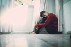 Young man sitting on the floor next to a window his head on his knees eyes closed experiencing caregiver burnout