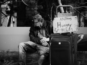 Homeless man sleeping sitting up with a sign that reads Hungry. What does a Traumatic Injury Actually Cost