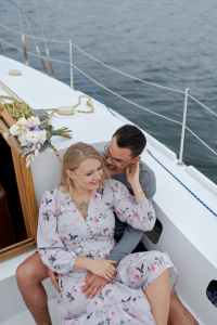 cheerful couple embracing on yacht sailing on ocean