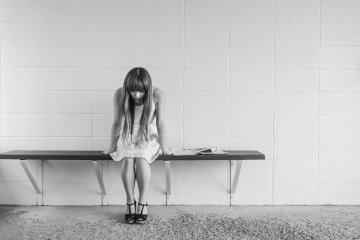 sitzende traurige Frau mit Blick auf den Boden