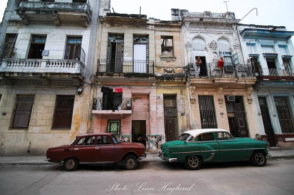 Cars parked in front of pastel colored houses in Havana