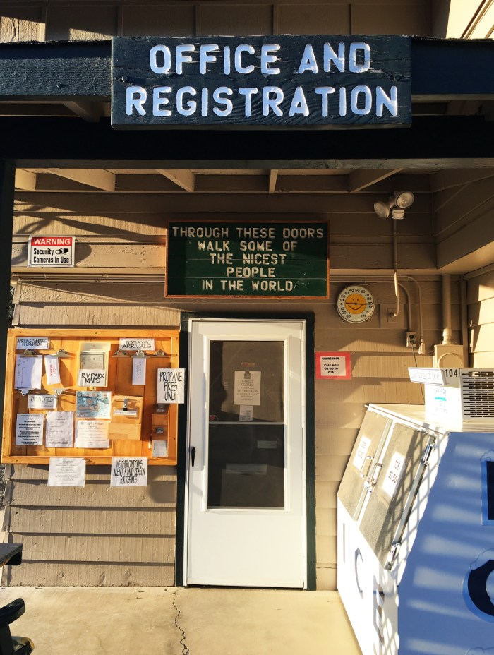 """Office at Crooked River Ranch RV Park where a sign says """"through these doors walk some of the nicest people in the world"""""""