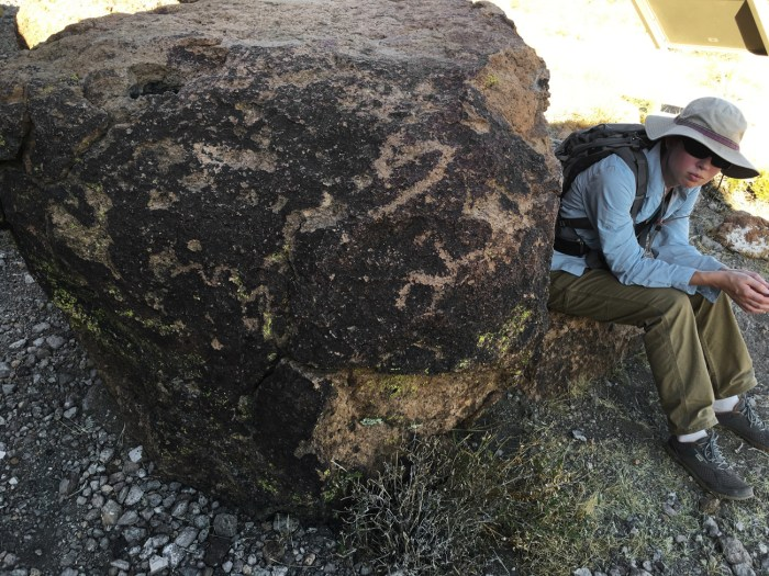Christina sitting next to a boulder with petroglyphs near the end of the Barber Peak Loop Trail