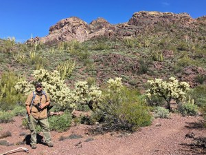 Michael standing on the edge of Bull Pasture Trail with jumping cholla and desert mountains in the background