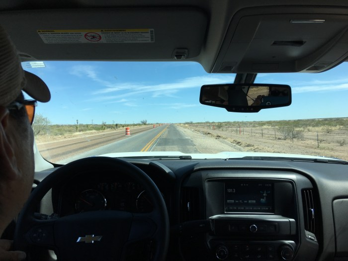View of the narrow, bumpy road and desert landscape through the windshield of our truck