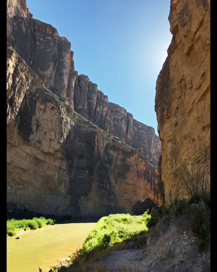 View inside Santa Elena Canyon bordered by a sheer cliff on either side and olive green water at the bottom