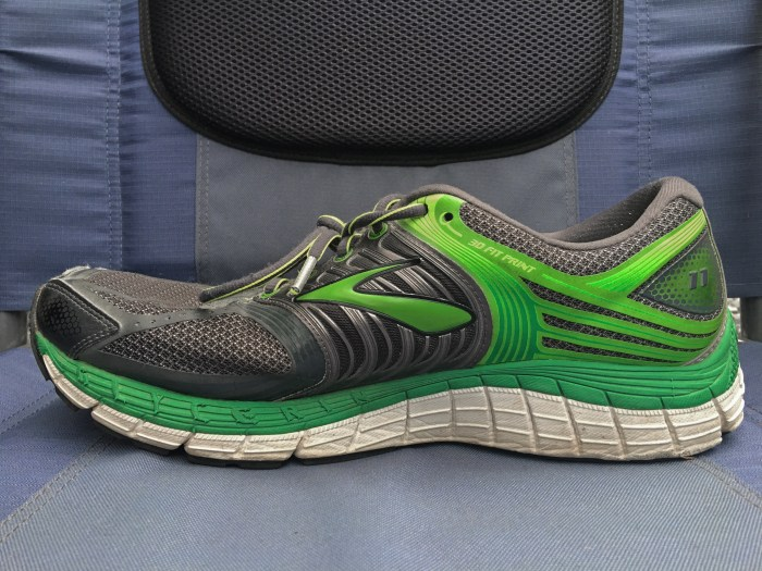 Conventional running shoe viewed from the side showing an elevated heel and upturned toe box