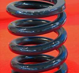 Picture of a very large spring. A car's suspension springs must be very large to support the weight of the vehicle and its cargo.