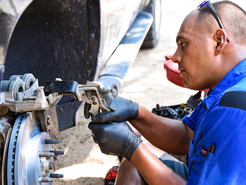Brakes To Go Technician works with tool while doing a brake repair