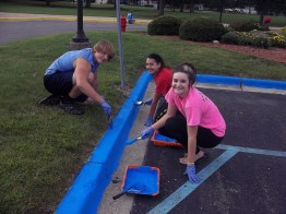 students painting a curb blue
