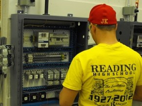 student posing with electrical panel