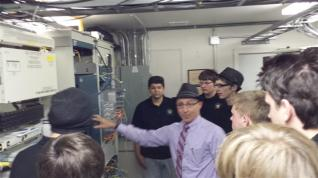 Amrtly dressed man showing network wiring to students