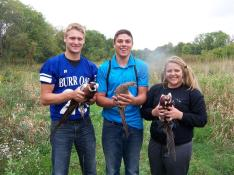 3 students posing with pheasants