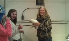 2 students posing with a chicken
