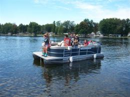 student on a pontoon boat taking water samples