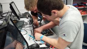 2 students changing laptop screen