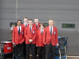 Students posing in red suitcoats and ties