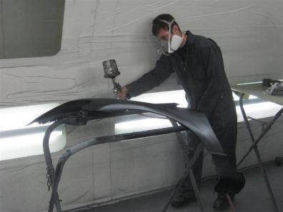 student spraying primer on fender