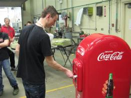 student purchasing cola form vintage machine