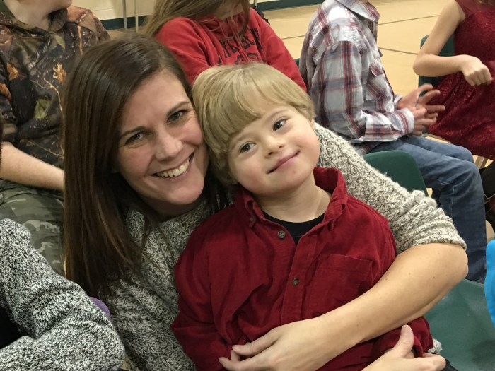 Jenn Clark, teacher, hugs a smiling young student, Blade Bovee, while smiling at the camera