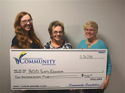 3 womesn holding large check