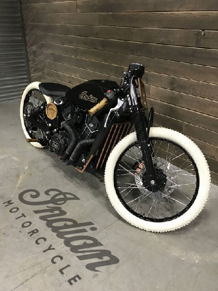 Indian Motorcycle. Cafe racer against wood wall, and on concrete floor Indian Motorcycle logo.