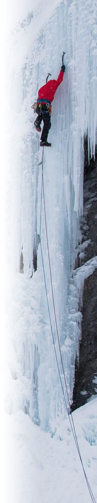 An ice climber going up an icicle on a cliff face.