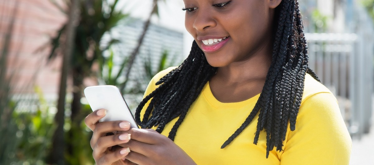 African american woman in a yellow shirt texting message with mobile phone with streets, trees and buildings in the background