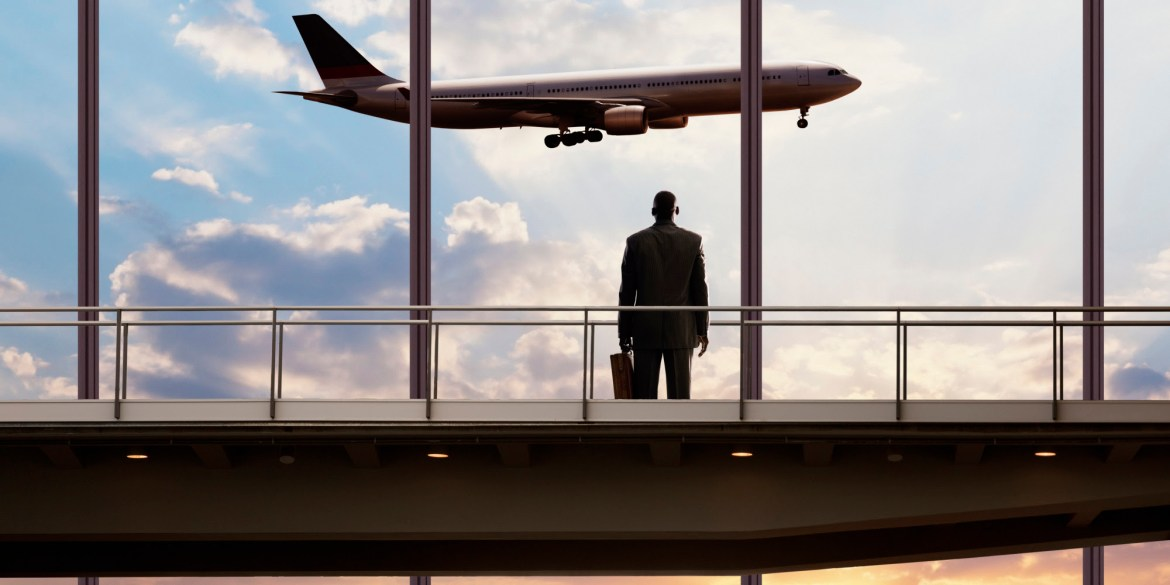 African American businessman watching plane in sky