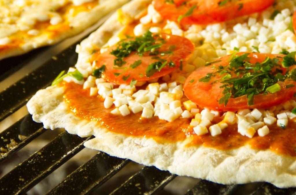 pizza napolitana con rodajas de tomate y perejil a la parrilla