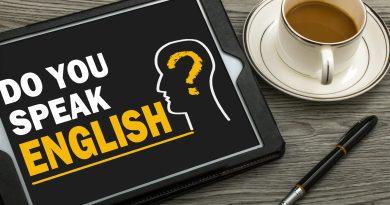"""Mesa de escritório com café, caneta e tablet com a pergunta """"do you speak english?""""."""
