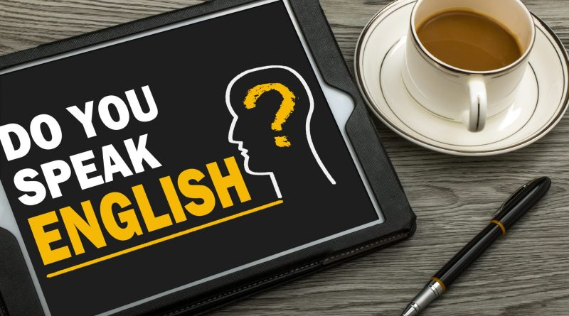 "Mesa de escritório com café, caneta e tablet com a pergunta ""do you speak english?""."