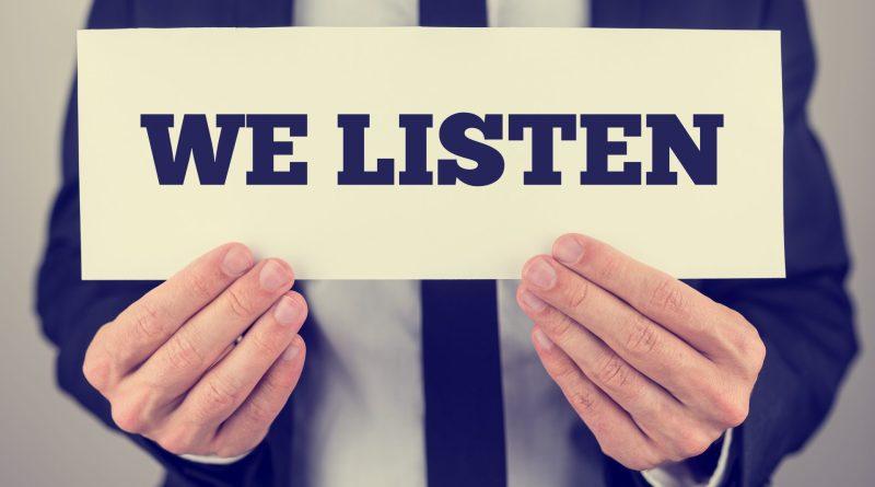 """Homem segurando uma placa com a frase """"we listen""""."""